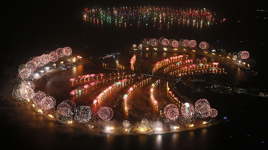 Fireworks explode over Palm Jumeirah in Dubai on Jan. 1, 2014, to celebrate the new year. Dubai's glittering fireworks display that lasted around six minutes spanned over 100 kilometres (60 miles) of the Dubai coast, which boasts an archipelago of man-made islands.